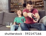cheerful father and son playing ... | Shutterstock . vector #592147166