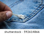 Small photo of Gum sticking on jean with holding hand of food stain on clothes of daily life