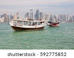 Stock photo boats with doha s panorama t the background 592775852