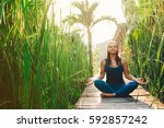 young woman practicing yoga... | Shutterstock . vector #592857242
