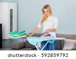 young smiling woman ironing... | Shutterstock . vector #592859792