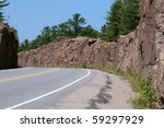 Two-lane road through Huckleberry Rock Cut in Muskoka - stock photo