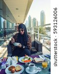 Small photo of lovely arabic lady having breakfast in nice marina view, wearing abaya and hijab