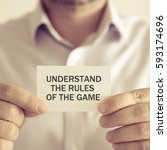 Small photo of Closeup on businessman holding a card with text UNDERSTAND THE RULES OF THE GAME, business concept image with soft focus background and vintage tone