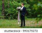 young beautiful groom in dark... | Shutterstock . vector #593175272
