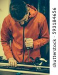 Small photo of Ski repair shop worker adjust the bindings and equipment. Winter workshop service