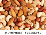 mix of nuts on a wooden table | Shutterstock . vector #593206952