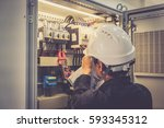 Technician is measuring voltage or current by voltmeter in control panel of power plant, selective focus on safety helmet - stock photo