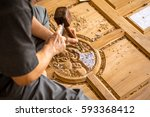 hand of carver carving wood | Shutterstock . vector #593368412