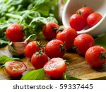 Cherry tomatoes  in a bowl with basil and garlic - stock photo