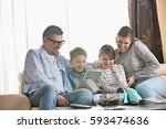 cheerful family using tablet pc ... | Shutterstock . vector #593474636