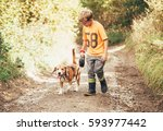 Stock photo boy walks with his beagle dog on the country road 593977442