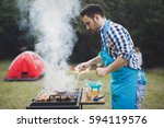 handsome male grilling meat for ... | Shutterstock . vector #594119576
