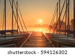 Tranquil and foggy sunrise at a small marina with sailing boats. - stock photo