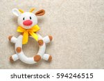 Stock photo amigurumi toy cow on a knitted background with copy space 594246515