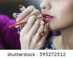 makeup artist applies lipstick. ... | Shutterstock . vector #595272512