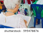 Small photo of old woman with white hair reading holy bible in a church