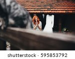 the bride stands near dress and ... | Shutterstock . vector #595853792