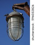 Small photo of hermetic waterproof street light with glass lampshade hanging on rusty metal bracket against the blue sky