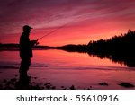 Fishing spinning at sunset. Silhouette of a fisherman - stock photo