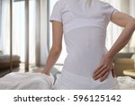 woman suffering from back pain... | Shutterstock . vector #596125142
