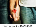 Small photo of red heart drawing on hands of a couple holding hand in hand, lovers, symbol of love, togetherness, hands holding, love, valentine