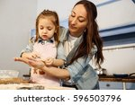 mother holding cookie on her... | Shutterstock . vector #596503796