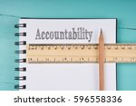Small photo of Accountability word on notebook, wooden ruler and pencil on blue wooden background. Top view. Business concept.
