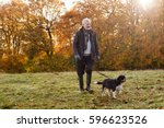 Stock photo senior man taking dog for walk in autumn landscape 596623526