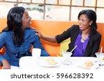 two women sitting in a... | Shutterstock . vector #596628392