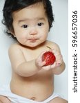 infant baby eating strawberry | Shutterstock . vector #596657036