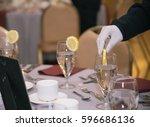waiter putting sliced lemon on... | Shutterstock . vector #596686136