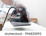woman uses irons  ironing at... | Shutterstock . vector #596820092