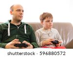 father and son playing video...   Shutterstock . vector #596880572