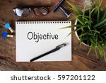 Small photo of Business Concept Top View Notebook Writing Objective
