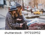 Small photo of Stylish city portrait of two fashionable girls trying to find the location on the map in Europe city centre .Fashionable friends traveling with backpack, map, camera, tourist, get a lost