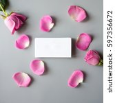Stock photo stack of white business cards with pink roses petals on gray background mock up for branding 597356672