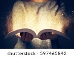 woman holding an open book with ... | Shutterstock . vector #597465842