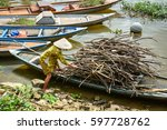 A Woman Carrying Wood By Boat...