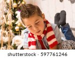 the boy at the christmas tree... | Shutterstock . vector #597761246