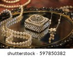 Small photo of Old metal tray with assortment of jewelry and box adorned with seed pearls