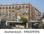 Small photo of Merv, Turkmenistan - 30 May 2015: Shabby, shoddy prefabricated soviet-era apartment blocks with multiple satellite TV dishes & clotheslines. Brick shed & disused bathtub in foreground