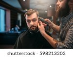barber trimming hair of the... | Shutterstock . vector #598213202