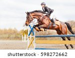Stock photo young horseback sportsgirl jumping over obstacles on show jumping competition 598272662