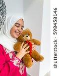 arabic girl with teddy bear | Shutterstock . vector #598458146