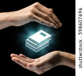 Small photo of Isolated image of two hands on black background. Pile of books icon in the center, as a symbol of library, knowledge. Concept of library, knowledge.