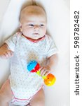 Small photo of Cute adorable newborn baby playing with lots of colorful rattle toys on white background. New born child, little girl looking surprised at the camera. Family, new life, childhood, beginning concept