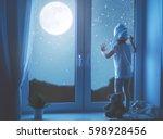 child little girl at the window ... | Shutterstock . vector #598928456