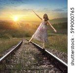 young girl goes on railway... | Shutterstock . vector #599000765