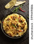 Small photo of Top view-Delicious homemade mutton or lamb dum biriyani over wooden background